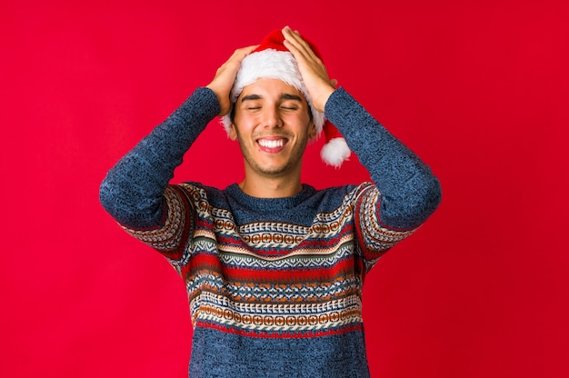 Young man on christmas day laughing keeping hands on heart, concept of happiness.