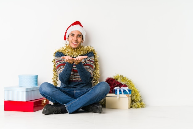 Young man on christmas day laughs and closes eyes, feels relaxed and happy.