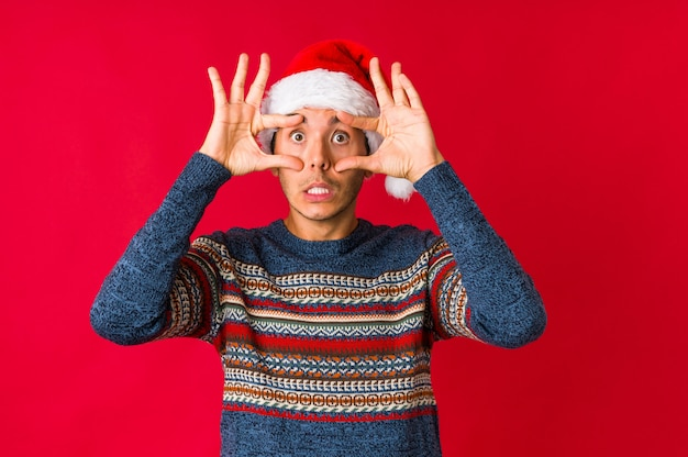 Young man on christmas day rejecting someone showing a gesture of disgust.