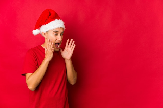 Young man on christmas day shouts loud, keeps eyes opened and hands tense.