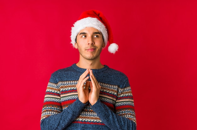 Young man on christmas day showing a dislike gesture, thumbs down. disagreement concept. assess