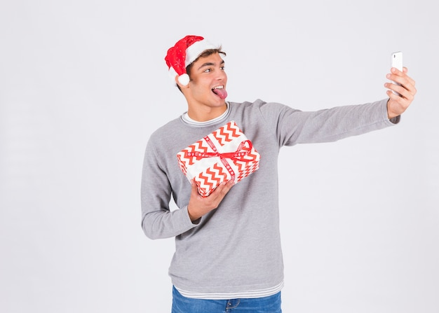 Young man in christmas hat with smartphone and present box
