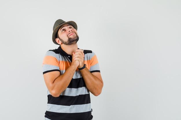 若い男は、tシャツ、帽子、希望に満ちた、正面図で祈りのジェスチャーで手を握りしめます。