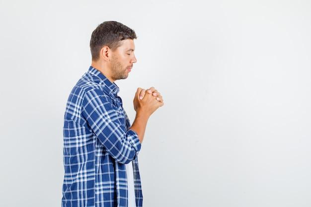 Giovane che stringe le mani nel gesto di preghiera in camicia e sembra speranzoso.