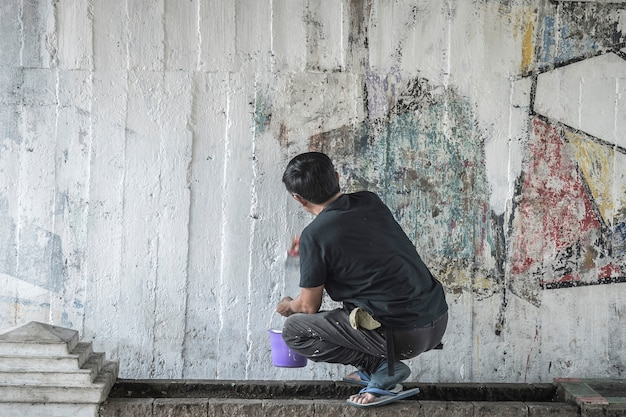 Young man clean the walls by painting white over the old cement wall.