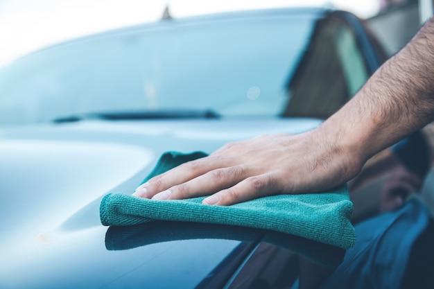 通りで車を掃除する若い男