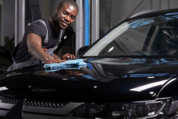 マイクロファイバーの布で車を掃除する若い男