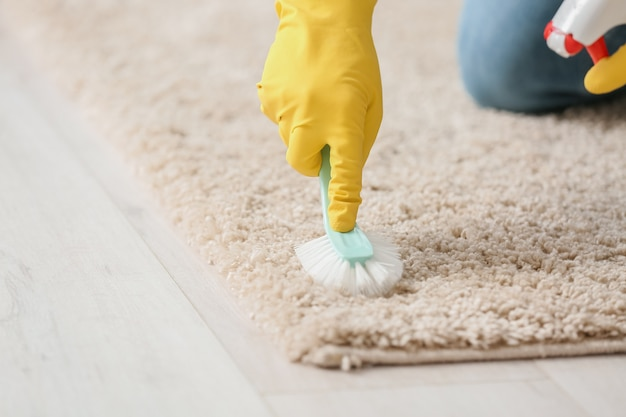 Молодой человек чистит ковер дома, крупным планом