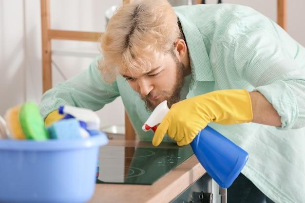 キッチンで赤外線炊飯器を掃除する若い男