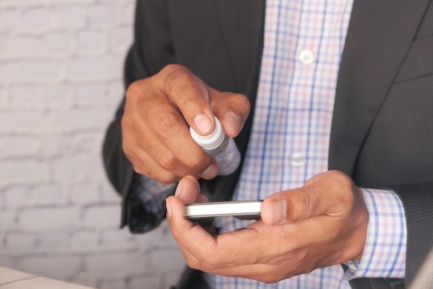 Молодой человек чистит дисплей мобильного телефона дезинфицирующим средством