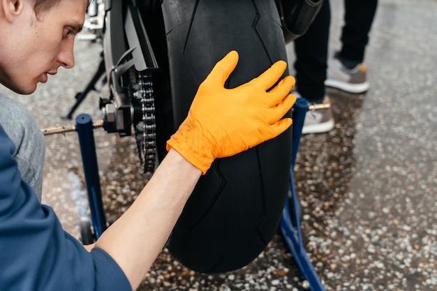 Молодой человек чистит или работает с современным мощным мотоциклом bmw black sportbike