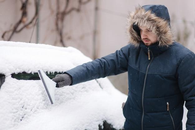 겨울 날에 차고 근처 야외에서 자동차 앞 유리에서 눈을 청소하는 젊은 남자