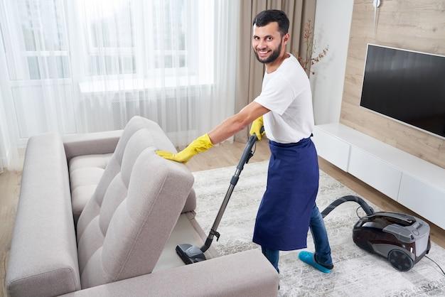 Молодой человек, чистящий диван с пылесосом в выходящей комнате дома