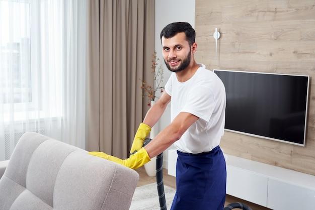 自宅の部屋を出て掃除機でソファを掃除する若い男