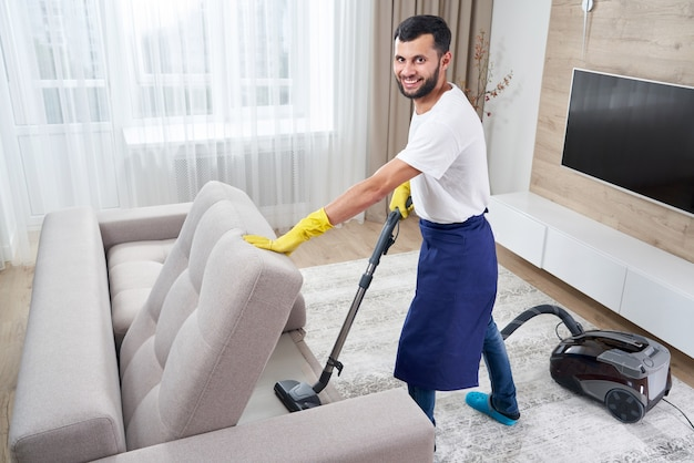 Young man cleaning sofa with vacuum cleaner in leaving room at home