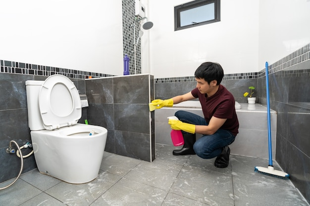 自宅のバスルームを掃除する若い男