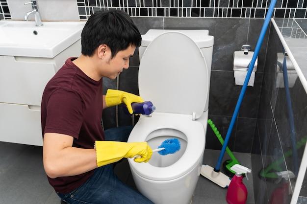 浴室の便器を掃除する若い男
