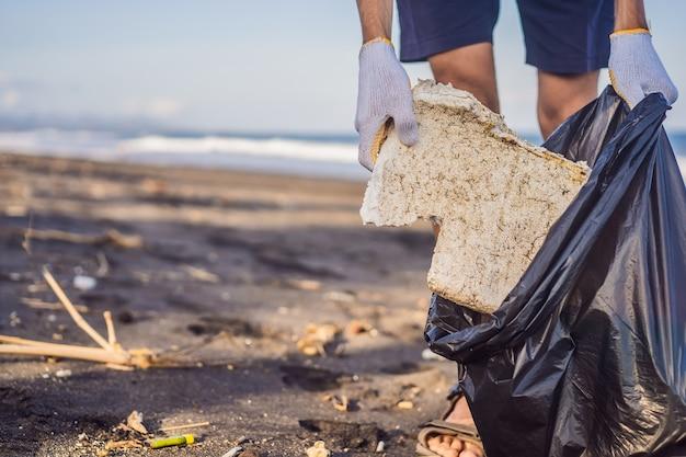 子供のビーチ自然教育を片付ける若い男