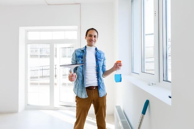 사무실에서 창문을 청소하는 젊은 남자