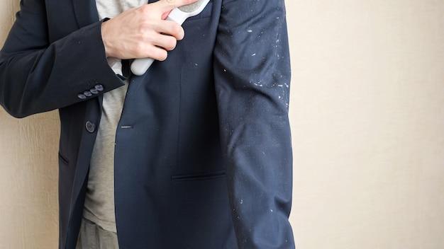 젊은 남자는 밝은 방 클로즈업에서 베이지색 벽 근처에 서 있는 정전기 의류 머리 제거 브러시로 흰색 동물의 머리카락에서 검은색 재킷을 청소합니다.