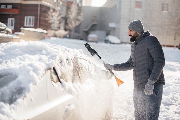 A young man cleans his car after a snowfall on a sunny, frosty day.