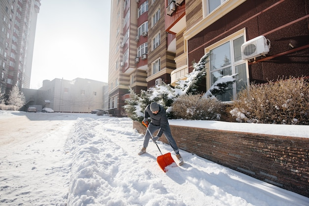 A young man clears the snow in front of the house on a sunny and frosty day. cleaning the street from snow.