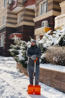 A young man clears the snow in front of the house on a sunny and frosty day.