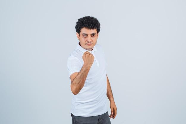 Молодой человек сжимает кулак в белой футболке и джинсах и выглядит серьезным, вид спереди.