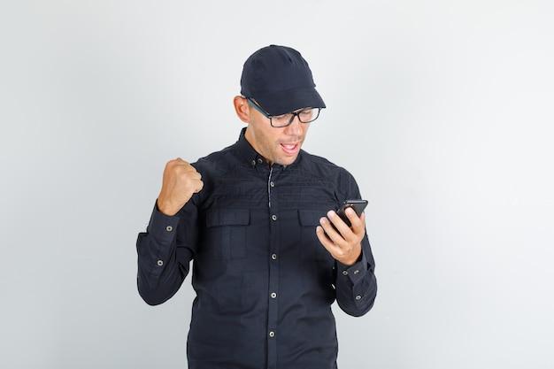 Молодой человек сжимает кулак со смартфоном в руке в черной рубашке и кепке