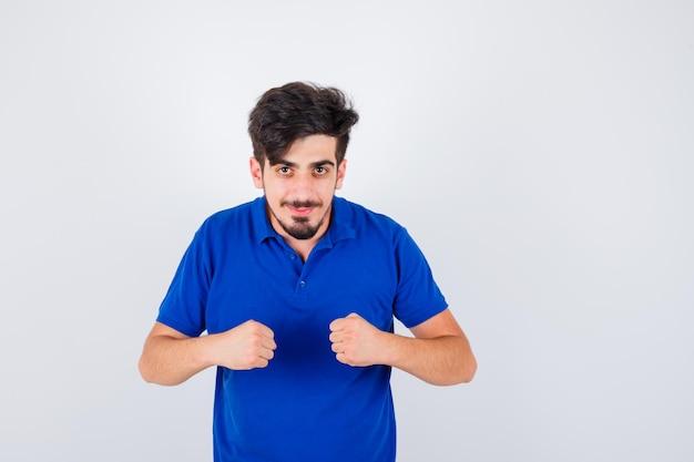 青いtシャツで拳を握りしめ、真剣に見える若い男