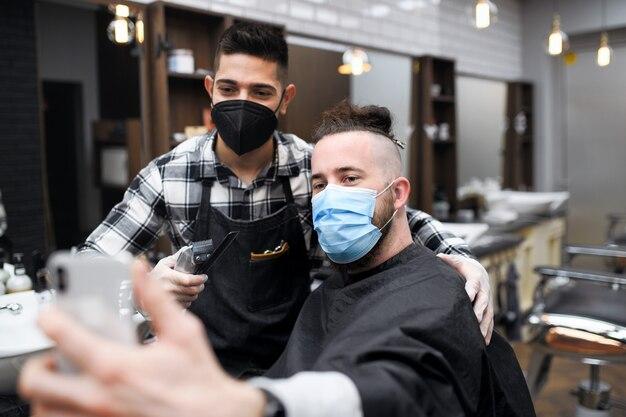 理髪店でハイドレッサー、コロナウイルス、新しい通常の概念で自分撮りをしている若い男性のクライアント。