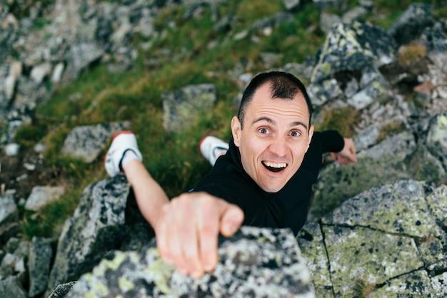 若い男が山の急な壁を登る。ロッククライムエクストリームスポーツ。ハイキングや山に登る観光客の男。夏の旅行アドベンチャー。