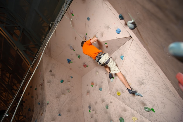 Young man climbing on practical wall in gym, bouldering