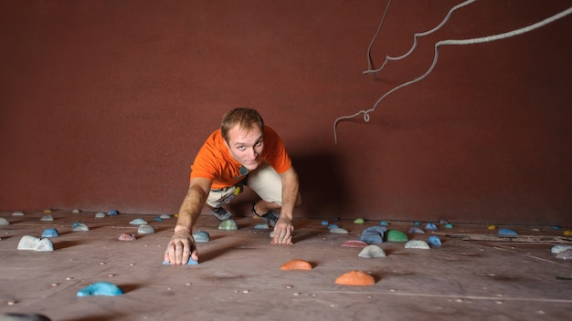 Young man climbing on practical wall in gym