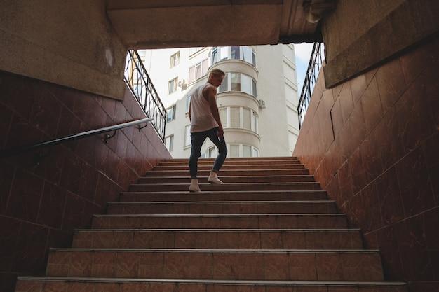若い男が歩行者の地下鉄で階段を登る