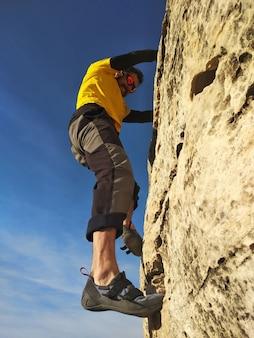 Молодой человек поднимается на скалистую стену