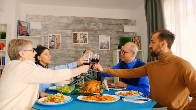 夕食を楽しみながら家族と一緒にグラスワインをチリンと鳴らす青年。