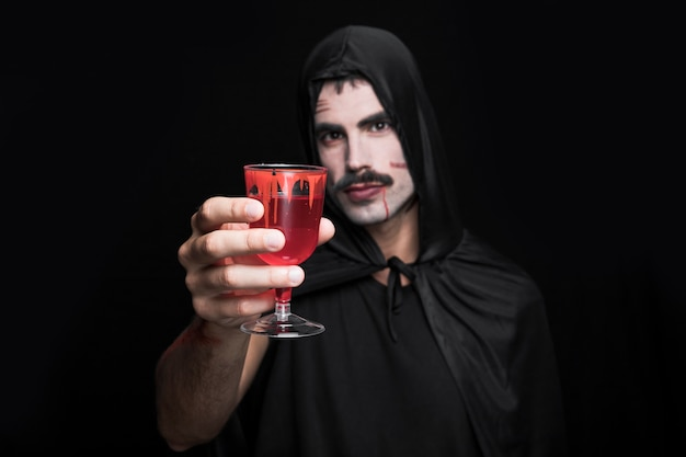 Young man in cloak with hood posing in studio with glass of red liquid
