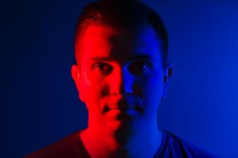 Young man close head portrait red blue double colors light
