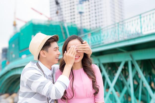 Молодой человек закрывает глаза девушке, чтобы сделать ей сюрприз - концепция любви, праздника и людей