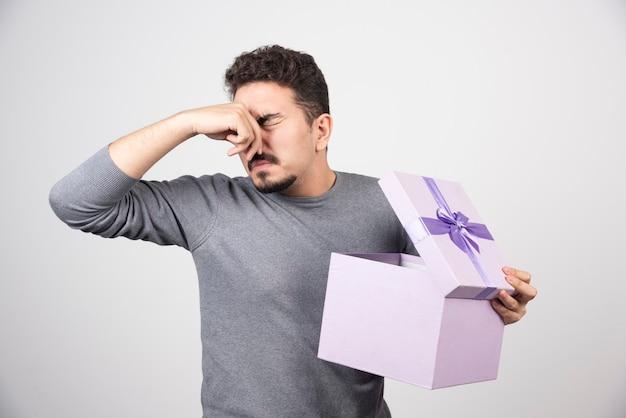 若い男は彼の鼻を閉じて、開いた紫色の箱を持っています。