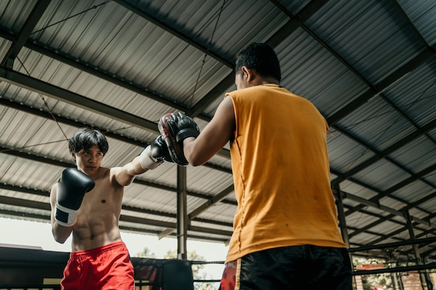 Young man and coach training together with punching pads on the boxing ring at training camp