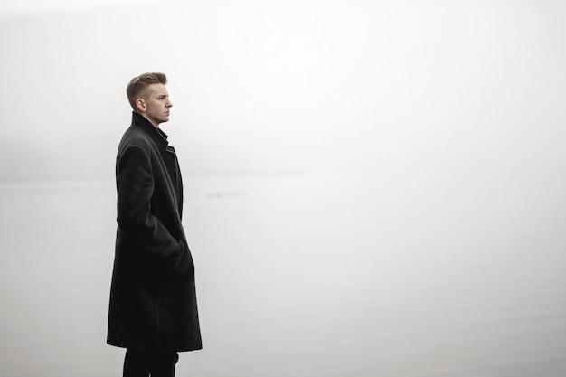 Young man in coat autumn sea fog