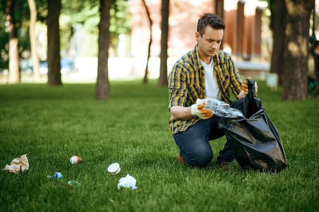 Young man collects garbage in a bag in park, volunteering. male person cleans forest, ecological restoration, eco lifestyle, trash collection and recycling, ecology care, environment cleaning