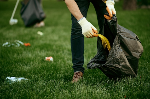 Young man collects garbage in a bag in park, volunteering. male person cleans forest, ecological restoration, eco lifestyle, trash collection and recycling, ecology care