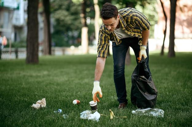 Молодой человек собирает мусор в мешок в парке, волонтерство