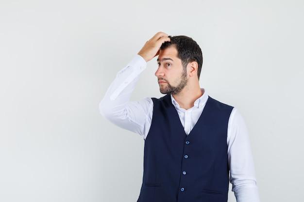 Молодой человек расчесывает волосы пальцами в рубашке, жилете и выглядит стильно