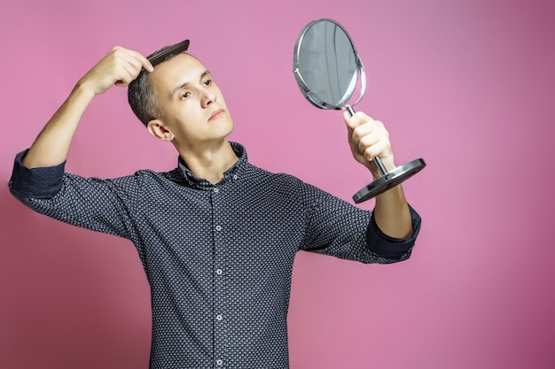 Young man combing his hair in front of a mirror on a pink background.