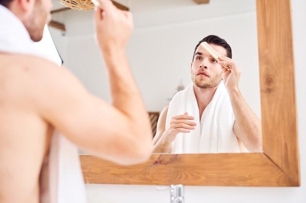 お風呂で鏡のそばに立っている間彼の髪をとかす若い男