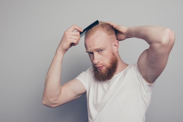 Молодой человек, расчесывающий волосы